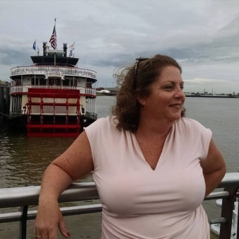 Photo of Angela at the New Orleans riverwalk, looking off screen to the right with a river boat in the background